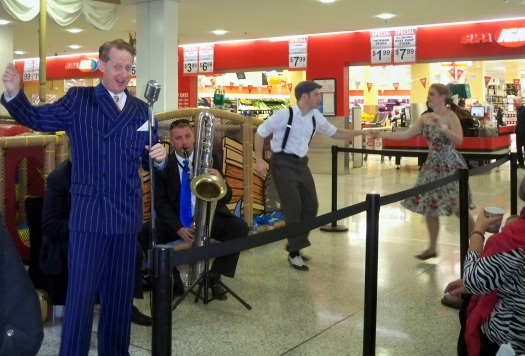 Greg Poppleton singing the songs of the 1920s in the Bakelite Broadcasters at Castle Mall. In picture: Greg Poppleton (mic) Chuck Morgan (banjo & uke) Richard Booth (soprano and bass saxes). Dancers: SwingKatz