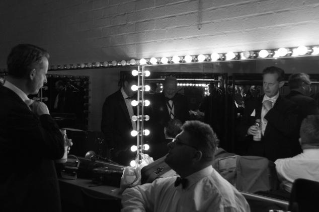Greg Poppleton (1920s singer) adjusts white tie in mirroe. Rod Herbert (sousaphone) looks on