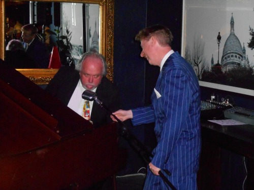 1920s-30s singer Greg Poppleton passes the birdcage mic to accompanist Tony Gardner, blowing a raspberry to punctuate a cheery performance of Tea For Two.