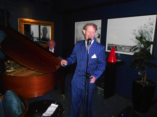 Swaying while crooning the art deco whimsy of 'Tip Toe Through The Tulips'. Pianist, Tony Gardner, toured three times with Tiny Tim.