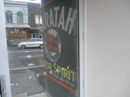 Recreated Waratah Motor Oil sign in its old location with King Street reflected on the glass door to a new commercial/residential building