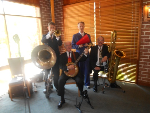 Greg Poppleton and the Bakelite Broadcasters snapped by a happy Riverbend diner. (L-r) Geoff Power (trumpet and the big silver sousaphone) Grahame Conlon (tenor banjo) Greg Poppleton (1920s vocals and megaphone) Jim Elliott ( clarinet, alto sax and the massive golden bass saxophone)