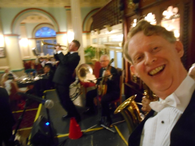 An on-stage selfie. Greg Poppleton and the Bakelite Broadcasters at the 2015 Great Art Deco Ball, Carrington Hotel, Katoomba. Greg Poppleton singer (white bow tie) Grahame Conlon banjo, Geoff Power trumpet (also sousaphone) Jim Elliott (behind Greg) bass sax, alto sax, clarinet.