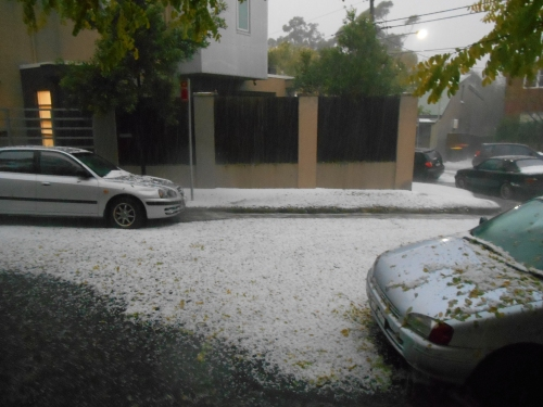 Hail falling and masses of water rushing down the gutters.