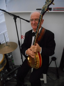 Grahame Conlon with a banjo on his knee. Grahame is well-known as a hot jazz guitarist. And he strums a mean ukelele.