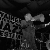 Greg Poppleton singing The Charleston through the big, red 1920s megaphone on the stage at Waiheke