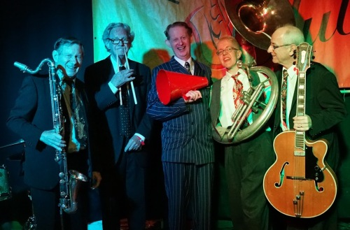 Greg Poppleton and the Bakelite Broadcasters (l-r) Paul Furniss (holding a bass clarinet) Lawrie Thompson (drums) Greg Poppleton (singer with megaphone) Cazzbo Johns (sousaphone) Grahame Conlon (guitar doubling banjo).