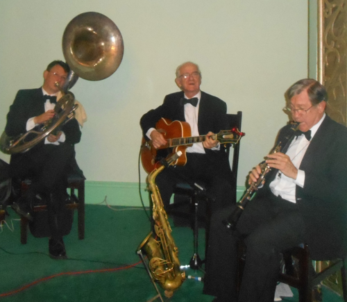 Greg Poppleton and the Bakelite Broadcasters on stage without Greg Poppleton who took the photo. In this 1920s Great Gatsby quartet, Greg Poppleton 1920s vocals, Geoff Power (sousaphone doubling trumpet) Grahame Conlon (guitar doubling banjo) and Paul Furniss clarinet doubling alto sax.)