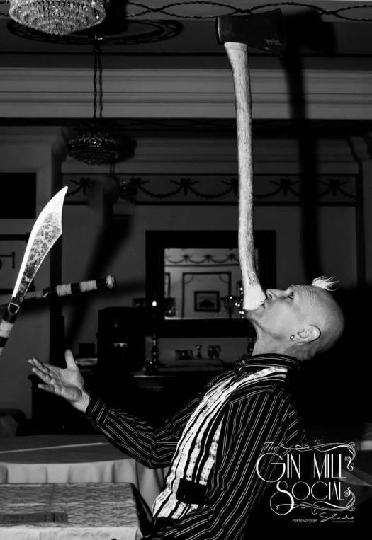Finhead juggles knives while balancing an axe