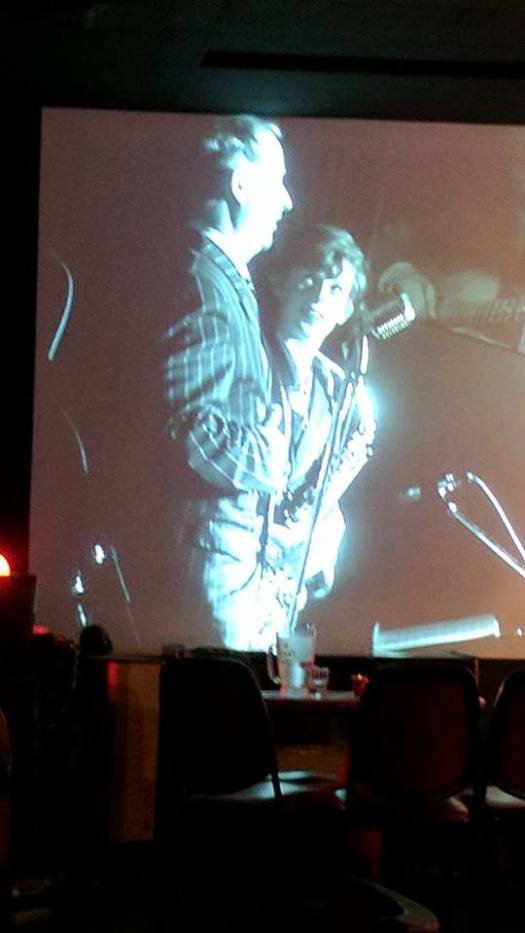 Greg Poppleton singing 'Button Up Your Overcoat' on the big screen with Damon Poppleton watching.