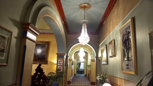 Inside the Carrington Hotel. The Grand Dining Room where the Art Deco Ball is held is through the archway on the left. The Billiard Room and Library are down the hall. The black and white photo hanging on the wall on the right is of an entertainment troupe at the hotel in 1906.