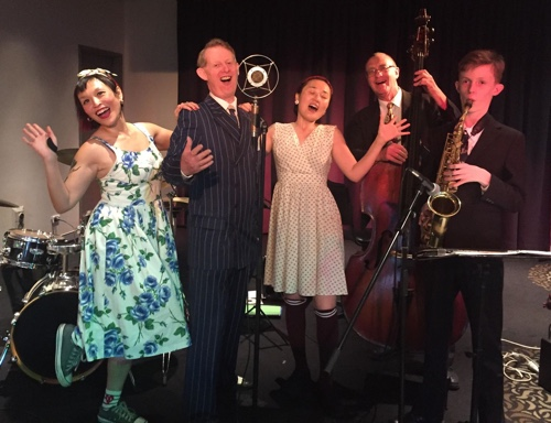 Swing dancers Sue Ann and Sandy pose with singer Greg Poppleton, Dave Clayton double bass and Damon Poppleton alto sax.