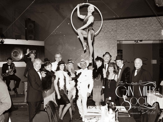 Greg Poppleton waves from behind the vintage mic as a group of Gin Mill Socialites gather for a photo  under Missy on the hoop.